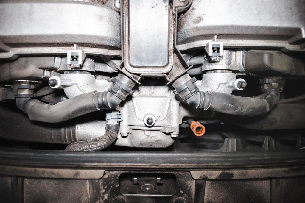 Термостат Ауди А8 скрывается под пластиковым щитком, сразу за решёткой радиатора