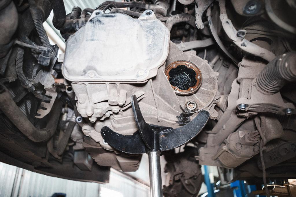 Подпираем гидростойкой коробку передач Шкода Октавия А5, откручиваем болты, извлекаем коробку из подкапотного пространства