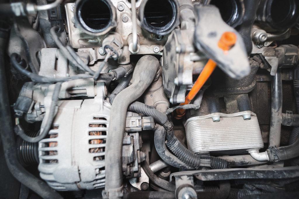 Старый термостат Фольксваген Пассат прячется за генератором и патрубками